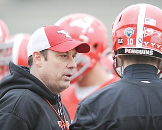 Youngstown State offensive coordinator Shane Montgomery talks to quarterback Ricky Davis between plays during the team's first practice of 2014 Saturday at YSU's Stambaugh Stadium. Davis, a redshirt freshman, is one of four players battling this spring to replace Kurt Hess as starting quarterback. The competition continued at Thursday's practice, which was the Penguins' first in pads.