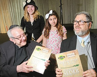 The Rev. George Balasko, left, and Rabbi Joseph Schonberger hold Haggadah, prayer books for the Seder meal, during the pre-Passover event Wednesday night at Stambaugh Auditorium in Youngstown. Sisters D'Ella, 14, and Millie Heschmeyer, 10, participated in the event. Sophia Brooks also sang.