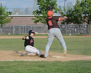 Girard baserunner Austin DeGregory slides into third base as East Palestine's Blaze Camberlain awaits a throw during Sunday's tournament game at Cene Park in Struthers. Girard won, 8-3, and advances to the Division III district semifinals to face South Range on Wednesday.