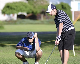 Katie Rickman | The Vindicator.Vince Goleno, 17, of Austintown (left) watches as Alec Hamilton, 15, also of Austintown putts during the Greatest Golfer Junior Qualifiers May 24, 2014.