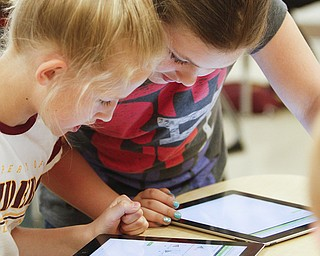 Fifth-graders Harley Novak, left, and Jillian Strecansky of South Range Middle School work on iPads during class. They use the devices to work on a math program that walks them through a tutorial to show them how to fix a problem they got wrong.