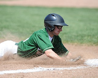 MASSILLON, OHIO - MAY 29, 2014: Base runner Zach Patton #20 of Ursuline slides head first into third base after a pass ball during a OHSAA tournament game at Massillon Washington High School. Ursuline won 7-5. (Photo by David Dermer/Youngstown Vindicator)
