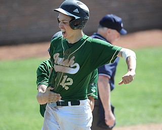 MASSILLON, OHIO - MAY 29, 2014: Base runner Gianni Quattro #12 celebrates after scoring the 6th and go-ahead run of the game, while being grabbed by teammate John Hintz #7 during a OHSAA tournament game at Massillon Washington High School. Ursuline won 7-5. (Photo by David Dermer/Youngstown Vindicator)