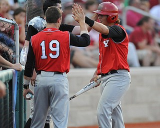 BLOOMINGTON, INDIANA - MAY 30, 2014: Base runner Brent Gillespie #11 of Youngstown State is congratulated by teammates Jared Wight #27 and Alex LArivee #19 after scoring the second YSU run of the game during Friday nights regional tournament game against Indiana University. (Photo by David Dermer/Youngstown Vindicator)