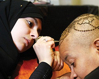Lamia Alfares, a local Henna artist, draws a Henna crown on the head of Monaca Beasley-Martin at the Calvin Center in Youngstown. Beasley-Martin has alopecia, a condition in which a person is allergic to his or her own hair and becomes bald.