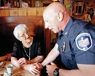 Liberty Police Chief Richard Tisone talks to resident Ann Brown during the annual Senior Watch breakfast Tuesday at West Fork Roadhouse on Belmont Avenue. The program offers seniors wellness checks, lockboxes at their homes for emergency crews, and smoke detectors. The breakfast is an invitation-only event for the program's participants.