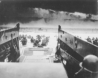 In this image provided by the U.S. Coast Guard, while under attack of heavy machine gun fire from the German coastal defense forces, these American soldiers wade ashore off the ramp of a U.S. Coast Guard landing craft, during the Allied landing operations at Normandy, France on June 6, 1944. (AP Photo/U.S. Coast Guard)
