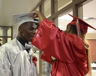 Katie Rickman   The Vindicator.Ta'Kora Nall (on right) fixes the hat of James Gordon prior to commencement at Chaney High School June 6, 2014.