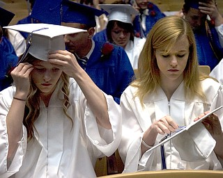 Kelli Cardinal/The Vindicator.Graduate Kayle Augustine, right, fixes the tassel on her cap Sunday next to her twin sister Jessica before walking into the fieldhouse for commencement at Poland Seminary High School.