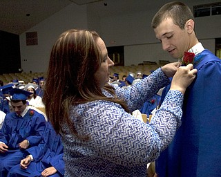 Kelli Cardinal/The Vindicator.Graduate Ryan Burkert receives his red rose boutonniere Sunday from Julie Walsh, a family and consumer science teacher, before walking into the fieldhouse for commencement at Poland Seminary High School.