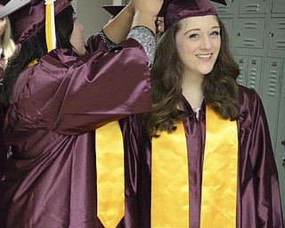 Katie Rickman | The Vindicator.Kristyn Wolf, on left, fixes the graduation cap of  Jenna DeLaurentis prior to the commencement ceremony at Boardman High School June 8, 2014.