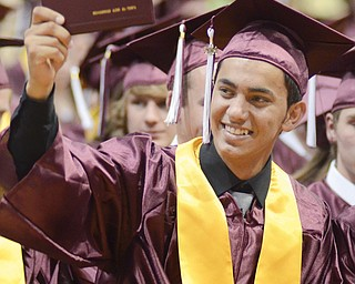 Mohammad Al-Tawil proudly shows his diploma during commencement Sunday in the Boardman High School gymnasium.