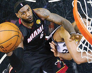 Heat forward LeBron James shoots over Spurs forward Tim Duncan during Sunday's NBA Finals game in San Antonio. James scored 35 points as Miami won to even the series.