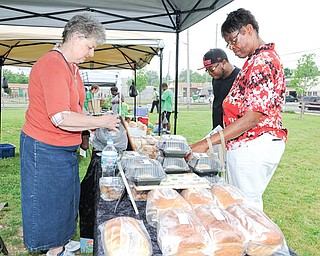Yvonne Howell and Jarell Houston, at right, both of Youngstown, check out the baked goods for sale by Shelli DelSignore from Shelli's Cookies at the Idora Neighborhood Farmers Market on Tuesday afternoon. The market at 2600 Glenwood Ave., on the city's South Side, will be open from 4:30 to 7:30 p.m. every Tuesday through Sept. 30.