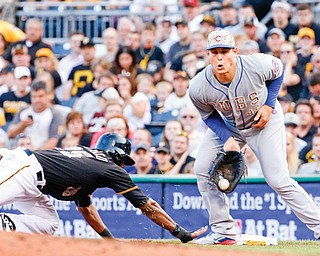 Chicago first baseman Anthony Rizzo, right, takes a throw from starting pitcher Travis Wood as Pittsburgh rookie Gregory Polanco dives back safely to first during the third inning Tuesday night. The Cubs beat the Pirates, 7-3.