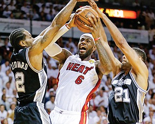 San Antonio Spurs forward Tim Duncan (21) and forward Kawhi Leonard (2) defend Miami Heat forward LeBron James (6) during the first half of Game 3 of the NBA Finals on Tuesday night.