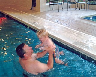 "Michael Billy, is coaxing his son, Gabriel, who just turned 2, to jump into the pool to ""Daddy will catch you. Don't be afraid."" After a few minutes he jumped. Taken at the Hilton Garden Inn in Blue Ash, Ohio, by Grandma Jean Billy."