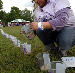 Kelli Cardinal/The Vindicator.Pam Jones, of North Lima, places names on the luminarias Friday during the 2014 Austintown Relay For Life event in Austintown Township Park.  The names are in honor or memory of those who have battled cancer.