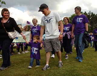 Kelli Cardinal/The Vindicator.Dalton Bodnar, center, 20-months-old, of Youngstown, walks the survivor lap Friday with mom Dana, and dad Michael during the 2014 Austintown Relay For Life event in Austintown Township Park.  Dalton Bodnar, who's been in remission for 8 months, was diagnosed with testicular cancer a week after his first birthday.
