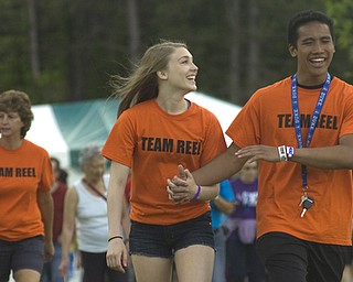 Kelli Cardinal/The Vindicator.Emma Hartshorn, 16, of Canfield, walks Friday with her boyfriend Kato Kim, 16, of Canfield, during the 2014 Austintown Relay For Life event in Austintown Township Park.  The couple was walking for former middle school teacher Ken Reel, who lost his battle with cancer.