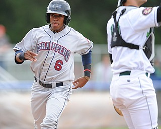 JAMESTOWN, NEW YORK - JUNE 13, 2014: Base runner Joel Mejia #6 of the Scrappers steps on home plate to score the first scrappers run of the game int he top of the 1st inning during a game at Russell Diethrick Park. (Photo by David Dermer/Youngstown Vindicator) Jamestown catcher Taylor Gushue #13 pictured.