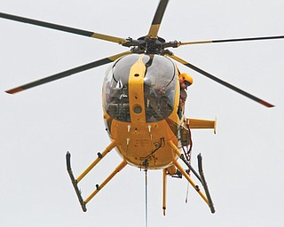 FirstEnergy of Northeast Ohio uses helicopters to build a 345-kilovolt power line running from Beaver County in Pennsylvania to Cuyahoga County. This process minimizes enviromental damage and proves to be more efficient for the company, FirstEnergy says. The workers in these photos are building the line in southern Mahoning County.