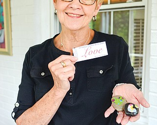 Mary Ann Dieter holds out Love Rocks made at the Paisley House in Youngstown recently. The concept of the rocks came from a personal tragedy that Dieter's family experienced.