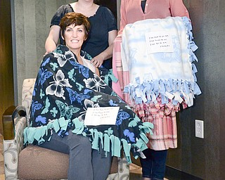 Sherrie Campana of Boardman, seated, is wrapped in a Blanket of Hope made by Emily Erb of Green Township, right, as her senior project at South Range High School. Emily was inspired to help cancer patients when Campana, a friend of her mother, Mary Kay Erb, left, was diagnosed with breast cancer.