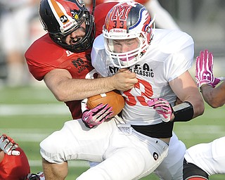 David Dermer | The Vindicator.Mahoning County's linebacker Nick Wells wraps up Trumbull County's running back James Cupan during the 2nd quarter of the Mahoning Valley Coaches Association's Jack Arvin Football Classic Thursday at Hubbard High School.