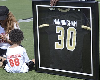 Katie Rickman   The Vindicator.Mario Manningham Jr. (left) sits next to his father's retired jersey at Warren G. Harding High School June 21, 2014. Mario Manningham's fiance Tiffany Hughley sits to the left of her son.