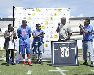 Katie Rickman   The Vindicator.Coach Arnold speaks during the jersey number retirement of Mario Manningham at Warren G. Harding June 21. From left to right: Anne Simpson (Mario's grandmother), Marion Manningham (Mario's mother), Mario Manningham, Coach Steven Arnold, and Kweisi Gharreau.