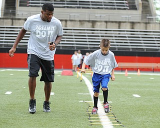 YOUNGSTOWN, OHIO - JUNE 21, 2014: Jordan Valdez works on quick feet in a rope drill with Brad Smith next to him encouraging him during the Brad Smith Football Camp at Stambaugh Stadium on the campus of Youngstown State Saturday morning. (Photo by David Dermer/Youngstown Vindicator)
