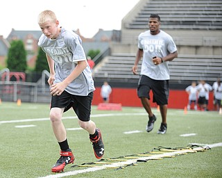 YOUNGSTOWN, OHIO - JUNE 21, 2014: Machael Johnson works on quick feet in a rope drill with Brad Smith next to him encouraging him during the Brad Smith Football Camp at Stambaugh Stadium on the campus of Youngstown State Saturday morning. (Photo by David Dermer/Youngstown Vindicator)