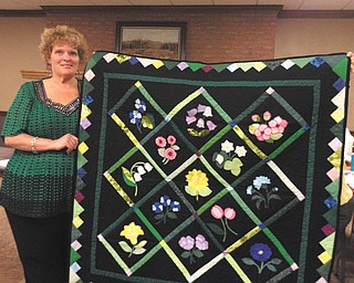 SPECIAL TO THE VINDICATOR Barbara King, assistant warden at Lorain Correctional Institution, displays a quilt made by a male inmate at the Grafton facility. A select group of inmates are chosen for the quilting program, and all quilts are donated to charities. King recently spoke to members of That Quilt Group I Belong To of Canfield and showed a variety of quilts made by the inmates. All of the fabric and supplies for the program are donated by quilt groups, quilt stores and individuals. No state funds are used.