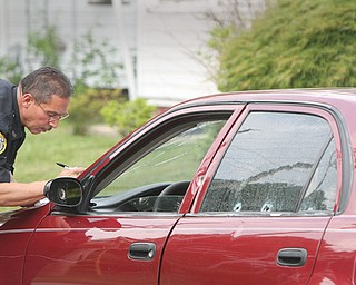 Pete Bonilla, a Youngstown police officer, inspects bullet damage to a car belonging to a man who was shot in the arm at Jackson Street and Himrod Avenue on Monday afternoon.