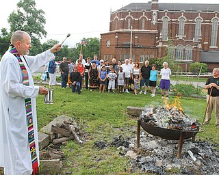 """The Rev. Ed Noga, pastor of St. Patrick Church, 1420 Oak Hill Ave., Youngstown, blesses the bonfire that is being used to burn """"torn and worn"""" religious articles. The occasion Monday was the vigil of the Feast Day of St. John the Baptist."""