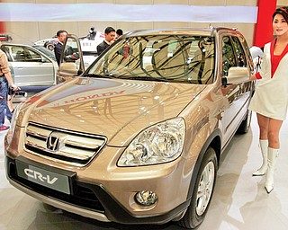A model poses by a Honda CR-V at Auto Shanghai 2005 exhibition in Shanghai, China. Honda, Mazda and Nissan are recalling millions of vehicles globally for defective airbags manufactured by supplier Takata Corp. that could possibly explode.