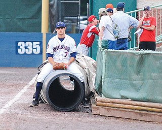 Scrappers outfielder Josh McAdams sits on the tarp during a rain delay prior to Tuesday night's game against the Batavia Muckdogs at Eastwood Field in Niles. Stormed continued to roll through the region, postponing the game until today when the teams will play a doubleheader. Game 1 will be at 5 p.m.