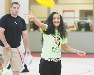 Robert Marino watches as Jaylene Varcas, 13, of Struthers tosses a Frisbee during the program. Each student took a turn tossing the Frisbee while other students measured the distance of the throw.