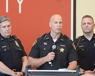 Mahoning County Sheriff Jerry Greene speaks as Canfield Police Chief Chuck Colucci looks on during Thursday night's sales-tax hearing at the Covelli Centre.