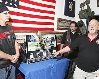 William d Lewis The Vindcaotr  Richard Watts of Girard speaks during a ceremony honoring 5 Girard men killed in Vietnam. At left is Landon McCauley, owner of Chestys Blue Collar Tavern in Girard where the event was held. At right is localartisit Ray Simon who created the artwork.