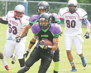 Scourge ballcarrier Brandon Rutland (5) looks for running room while being pursued by Cleveland Patriots KayRon Purdie (53 and Weadell Chery (80) during Sunday's game in Poland. Behind Rutland is Scourge teammate Jaymes Williams (8).