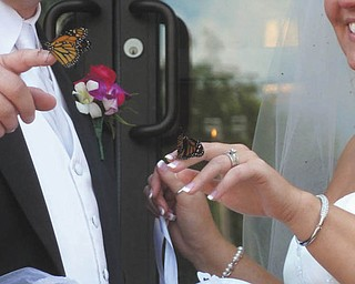 """Sue Drotleff of Salem submitted this photo from her daughter's wedding. Melanie Drotleff and Michael Hughes were married July 16, 2011, at Emmanuel Lutheran Church in Salem. Immediately after the ceremony, the couple released monarch butterflies signifying their new life together. Most of the butterflies took off immediately, but two had to be """"coaxed out"""" of the container by Melanie and Mike. The two butterflies perched on their fingers and stayed long enough for pictures followed by a shared kiss by the newlyweds; then the  butterflies flew away. It was beautiful!"""