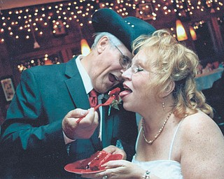 """Marshall and Christine Blaire are sharing a piece of their """"Red Solo Cup"""" cake at their wedding, Sept. 15, 2012. They met online Feb. 18, 2012."""