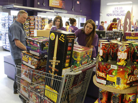 Gaven Hedrick of Erie, Pa., heads to the checkout at Phantom Fireworks in Youngstown with Annika Bunevich as Jessica Markowitz runs the scanner.  Phantom Fireworks is again the #1 shop to buy fireworks as the Valley gets ready for the big booming holiday.