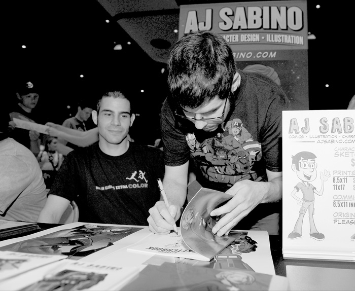 Local artist AJ Sabino of Cortland signs a piece of original artwork during the 2014 All-AmeriCon comic book convention. Rocco Sabino of Cortland also is pictured.