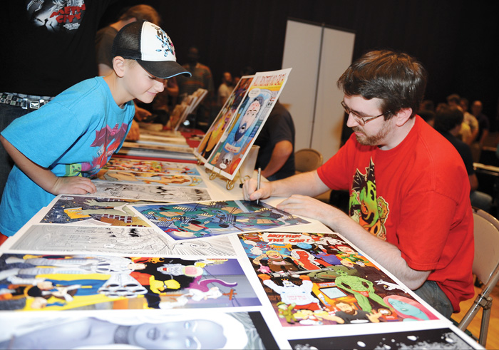 Comic-book artist George Graybill of Brookfield signs an original piece of artwork for Riley Russo 7, of Brookfield during the 2014 All AmeriCon comic book convention at Packard Music Hall in Warren.