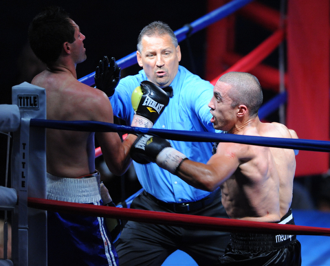 PITTSBURGH, PENNSYLVANIA - JULY 11, 2014: Referee Chris Riskys steps in to end the fight while Jake Giuriceo throws one final punch at Travis Hartman during a welterweight bout Friday night at Rivers Casino. Giuriceo would win via 4th round TKO. (Photo by David Dermer/Youngstown Vindicator)