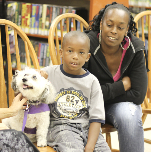 """Braylen Miller (middle) and his mother Monica Brown of Youngstown pet """"Meja"""", a 10 year old Schnoodle at the Brownlee Woods branch of the Public Library of Youngstown on Saturday afternoon.   Dustin Livesay  