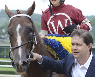 Katie Rickman   The Vindicator.Tapiture and his jockey Rosie Napravnik are led off the track by owner Ron Winchell after winning the West Virginia Derby August 2, 2014.